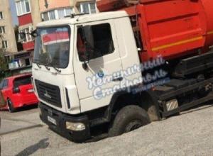 Мусоровоз застрял в огромной дыре на дороге в Ставрополе